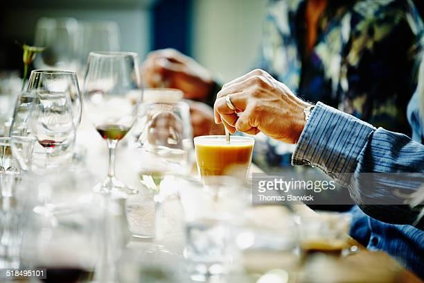 Close-up of mans hand stirring cream in coffee