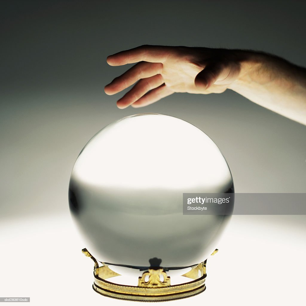 Close-up of man's hand touching crystal ball : Stock Photo