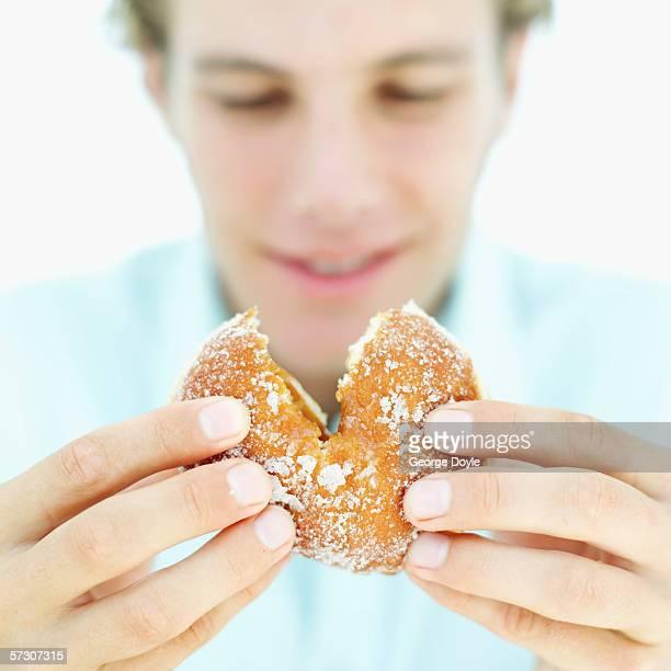 Close-up of man's hands breaking a doughnut