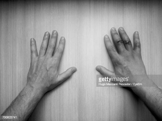 Close-Up Of Mans Hands On Wooden Surface