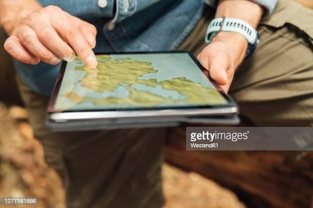 close-up of man's hands using map over digital tablet in forest - digital tablet stock pictures, royalty-free photos & images