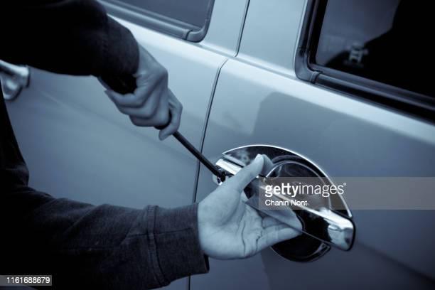 close-up of mans hands using screwdriver to break into car - steel stockfoto's en -beelden