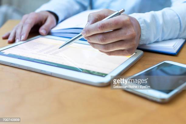 Close-Up Of Mans Hands Working On Tablet