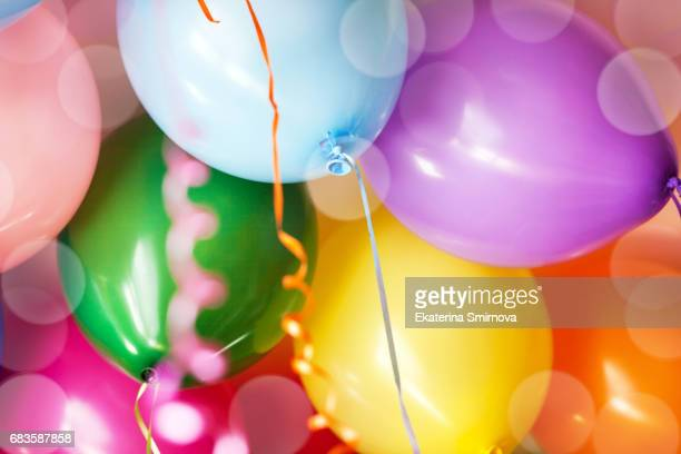 close-up of many bright colorful funny balloons under ceiling, as background - jahrestag stock-fotos und bilder