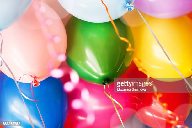 Close-up of many bright colorful funny balloons under ceiling, as background
