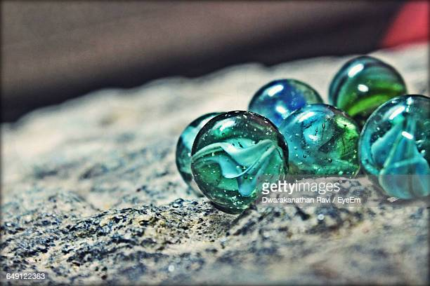 Close-Up Of Marbles On Rock