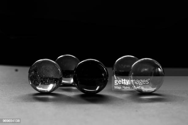 Close-Up Of Marbles On Table Against Black Background