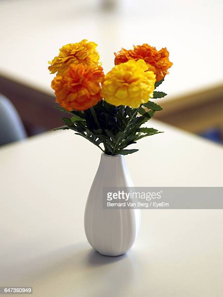 Close-Up Of Marigolds In Vase On Table