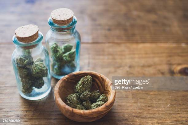 close-up of marijuana in jar on table - marijuana stock photos and pictures