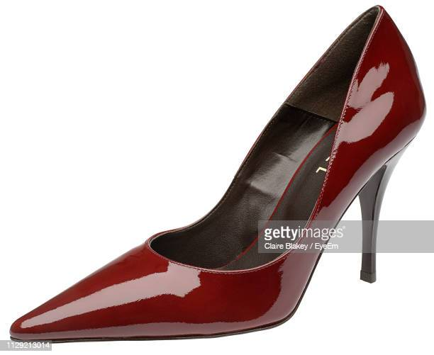 close-up of maroon stiletto over white background - stiletto stock pictures, royalty-free photos & images