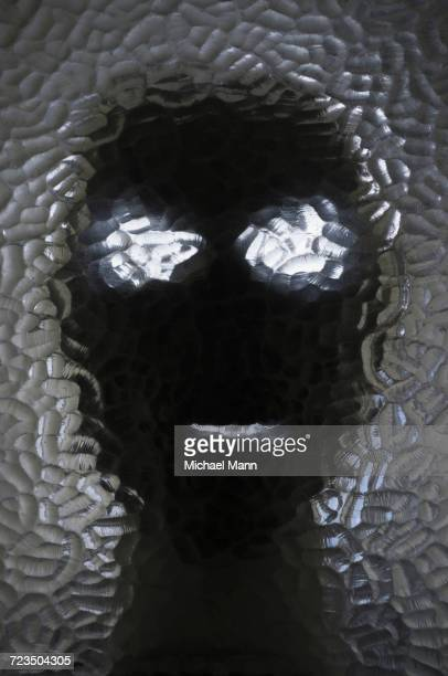 Close-up of mask seen through frosted glass