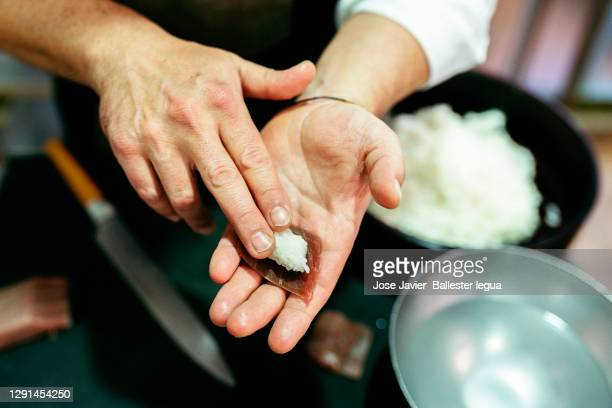 close-up of master chef itamae with blue fin tuna and rice cut on his hand for shusi, and nigiri. - nigiri stock pictures, royalty-free photos & images