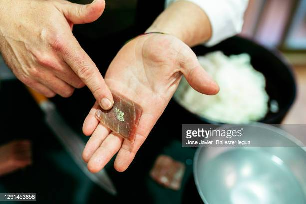 close-up of master chef itamae with blue fin tuna cut on his hand for shusi, and nigiri. - nigiri stock pictures, royalty-free photos & images