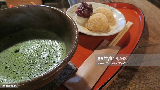 Close-Up Of Matcha Coffee With Cookies On Table