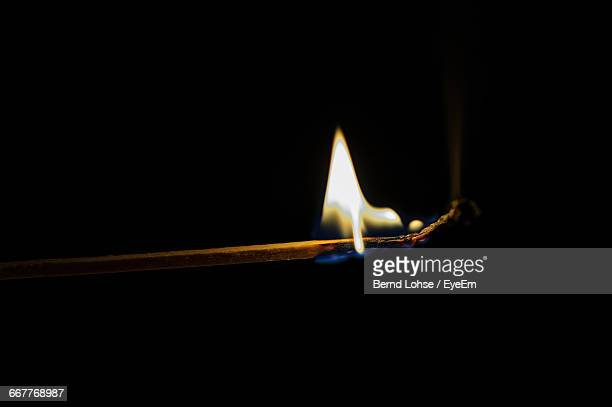 Close-Up Of Matchstick Burning Against Black Background