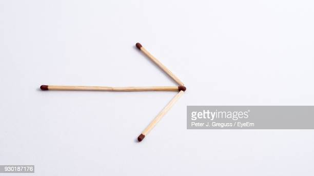 Close-Up Of Matchsticks Making Arrow Against White Background