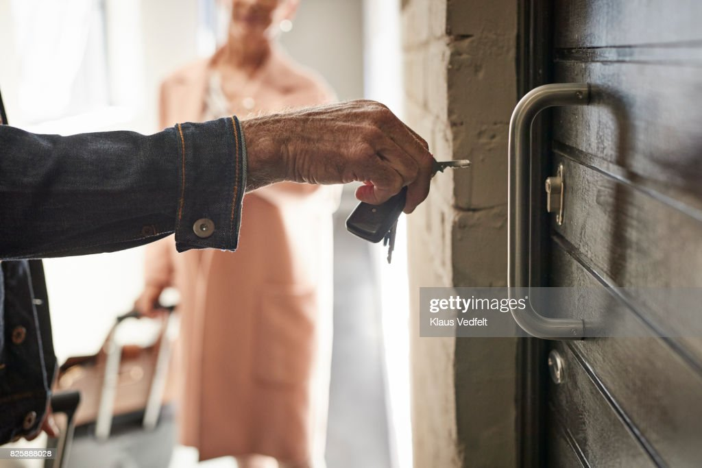 Close-up of mature couple opening door to holiday rental apartment with key : Stock Photo