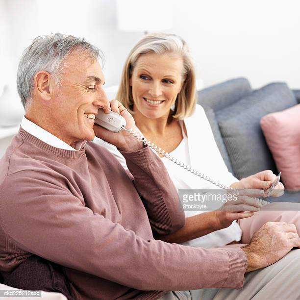 Close-up of mature couple sitting on sofa talking on telephone and holding credit card