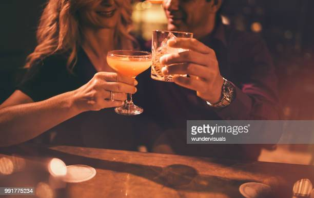 close-up of mature couple toasting with drinks at bar - cocktail party stock pictures, royalty-free photos & images