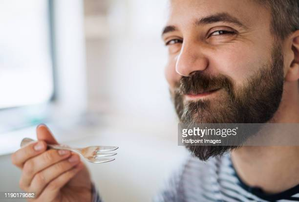close-up of mature man indoors at home, eating cake. - vergnügen stock-fotos und bilder
