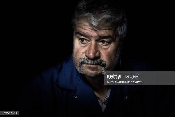 Close-Up Of Mature Man Looking Away Against Black Background
