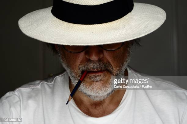 close-up of mature man wearing hat against wall - くわえる ストックフォトと画像