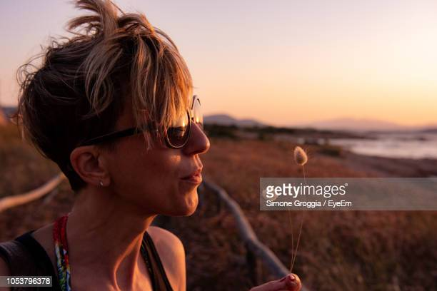 Close-Up Of Mature Woman Blowing Dandelion On Field
