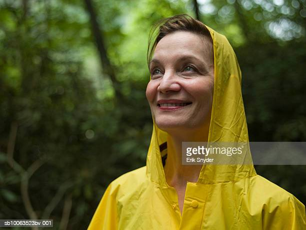 Close-up of mature woman in yellow raincoat, smiling