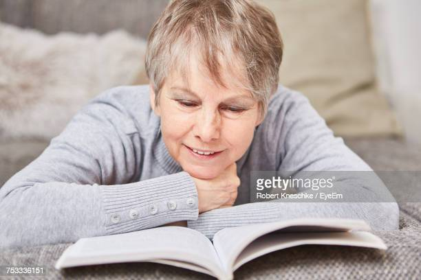Close-Up Of Mature Woman Reading Book While Lying Down On Sofa In Living Room At Home
