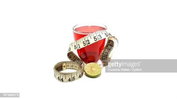 Close-Up Of Measuring Tape And Juice Against White Background