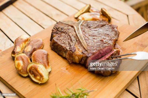 Close-Up Of Meat On Cutting Board Over Wooden Table
