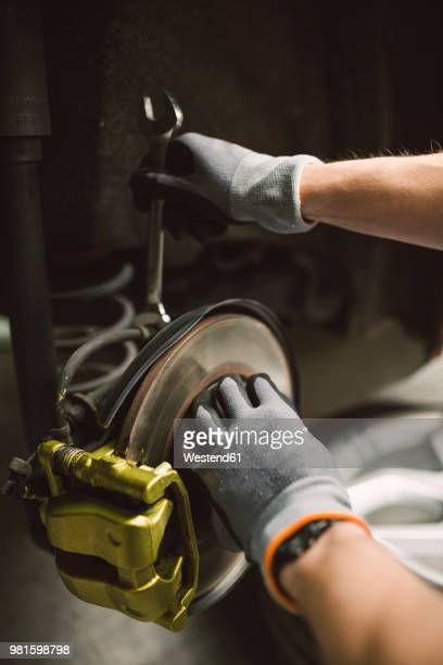 Close-up of mechanic fixing the brake caliper of a car in a workshop