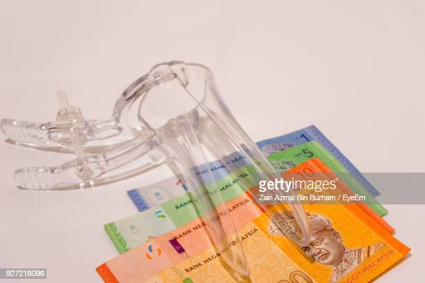 close-up of medical equipment on paper currency over white background - malaysian ringgit stock photos and pictures