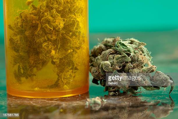 close-up of medical marijuana with orange jar full with it - medical cannabis stock photos and pictures