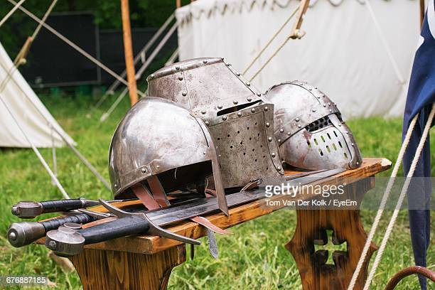 Close-Up Of Medieval Helmets And Swords On Table