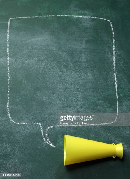 close-up of megaphone with speech bubble drawn on blackboard - announcement message stock pictures, royalty-free photos & images