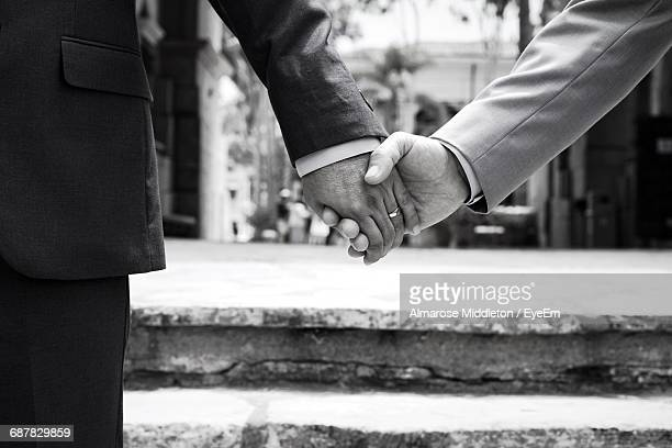 Close-Up Of Men Holding Hands