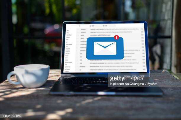 close-up of message icon in laptop on table - e mail inbox stock pictures, royalty-free photos & images
