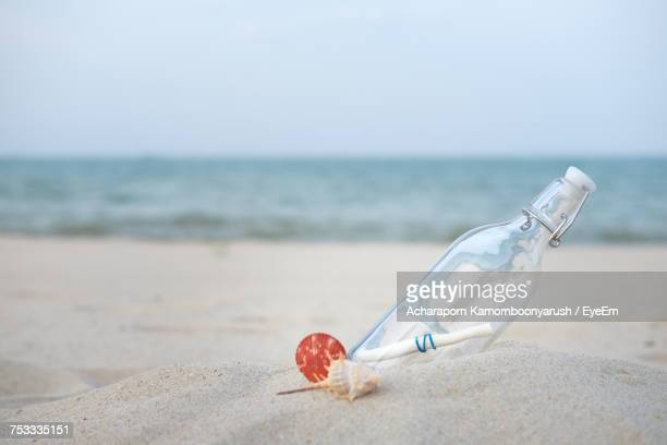 Close-Up Of Message In A Bottle On Beach Against Sky
