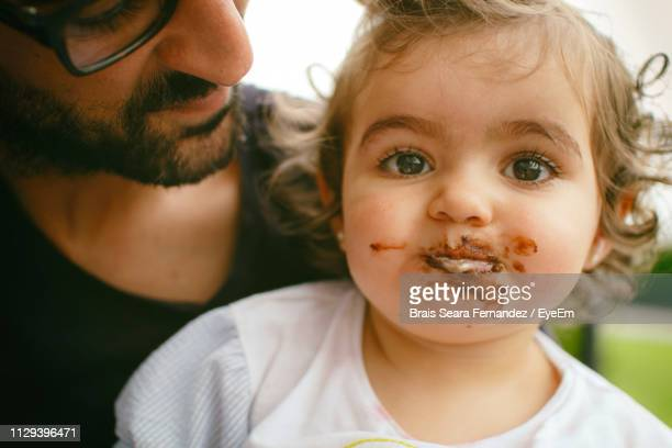 close-up of messy baby with father outdoors - 口を使う ストックフォトと画像
