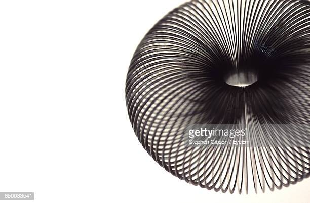 close-up of metal coil against white background - metal coil toy stock photos and pictures