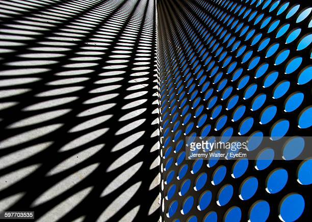 Close-Up Of Metal Grate With Shadow On Concrete Wall