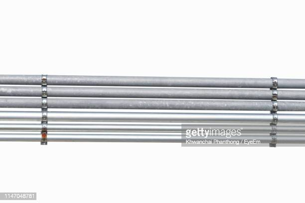 close-up of metal pipes against white background - pipe tube stock pictures, royalty-free photos & images