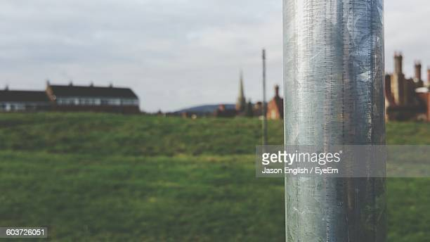Close-Up Of Metal Pole On Grassy Field Against Sky