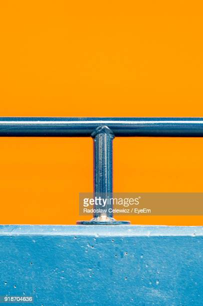 close-up of metal railing against orange background - parapetto barriera foto e immagini stock