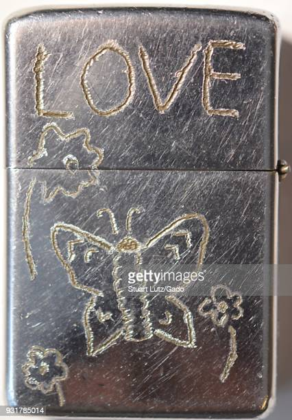 Closeup of metal Zippo lighter on which the owner has handengraved hippie symbolism including the word Love and a butterfly and flower motif during...