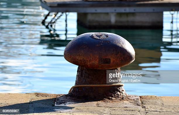 close-up of metallic bollard against sea on sunny day - bollard stock photos and pictures