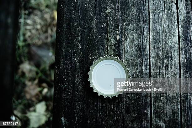 Close-Up Of Metallic Bottle Cap On Wood