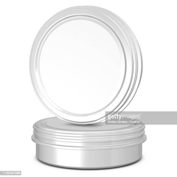 Close-Up Of Metallic Containers On White Background