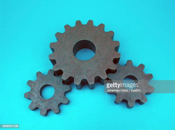 Close-Up Of Metallic Gears Against Blue Background